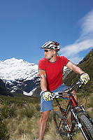 Cyclist sitting on bike in field