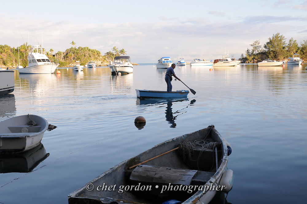 A man paddles a dinghy out to a sailboat moored at Ely's Harbor in Sandy's Parish, Bermuda on Wednesday, September 19, 2012.