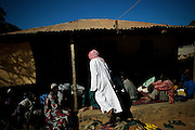 "People gathering around the holy man in Bafata-Oio village, Aladji Fode Mai Toure, expecting his blessing and listening to his advice. Locally known as ""Homem Grande"", meaning 'great man', serving as a community and local leader. Half of the population are considered to be muslim."