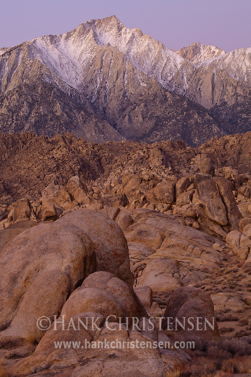 Dawn begins to light Lone Pine Peak and the wild rock formations of the Alabama Hills