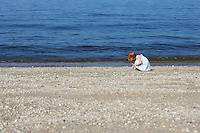 Young girl (5-6) squatting on beach