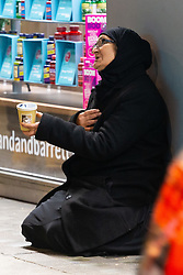 A woman begs outside one of the department stores on Oxfors Street. Homeless Britons are coming under increasing pressure as a surge of Roma beggars from Romania arrive on the streets of London to take advantage of the generosity of Christmas shoppers. London, December 04 2018.
