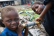 Children fill jericans with water from a pipe outside the Mboga primary school in the town of Kibati, on the outskirts of Goma, Eastern Democratic Republic of Congo on Friday December 12, 2008.
