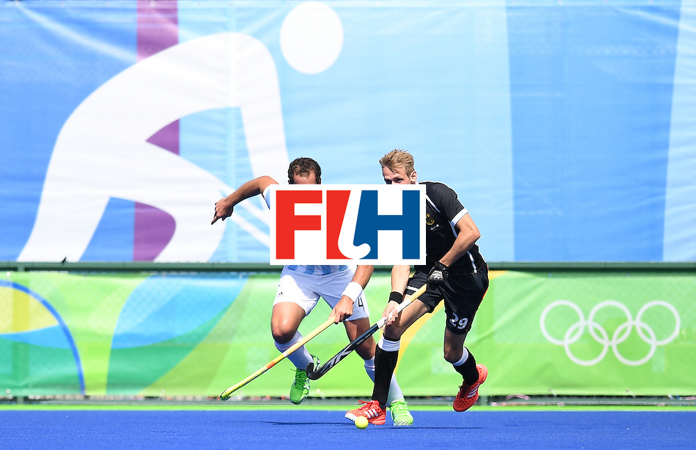 Argentina's Juan Gilardi (L) and Germany's Niklas Wellen vie for the ball during the men's field hockey Argentina vs Germany match of the Rio 2016 Olympics Games at the Olympic Hockey Centre in Rio de Janeiro on August, 11 2016. / AFP / MANAN VATSYAYANA        (Photo credit should read MANAN VATSYAYANA/AFP/Getty Images)