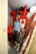 Michal, 33, artist in her storage in North London. She is on a waiting list for her own studio so she has to keep much of her work: creatures made from red PVC, stuffed like soft toys and huge photographs of women in fetish masks.