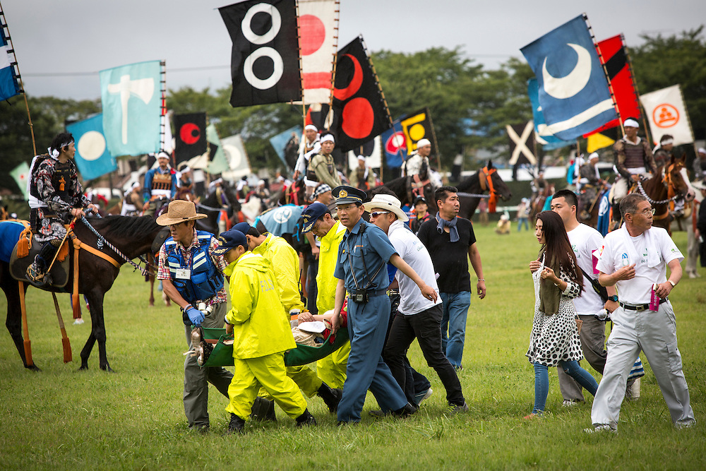 """MINAMISOMA, JAPAN - JULY 24 :  An injured samurai horseman who fell off his horse carried by paramedics in the Shinki-soudatsusen (sacred flag competition) during the Soma Nomaoi festival at Hibarigahara field on Sunday, July 24, 2016 in Minamisoma, Fukushima Prefecture, Japan. """"Soma-Nomaoi"""" is a three day traditional festival that recreates a samurai battle scene from more than 1,000 years ago. The festival has gathered more than thousands visitors as Fukushima still continues to recovery from the 2011 nuclear disaster, the samurai warriors battles for recovery of the area. (Photo: Richard Atrero de Guzman/NURPhoto)"""