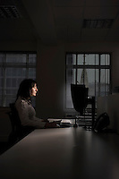 Female office worker using computer in darkened office side view