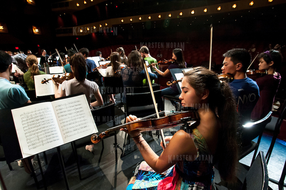 July 9, 2013 - Purchase, NY : Members of the National Youth Orchestra of the United States of America, including Julia Popham, foreground right, prepare for rehearsal with conductor Valery Gergiev (not pictured) at SUNY Purchase's Performing Arts Center in Westchester on Tuesday afternoon. The Orchestra, a new project of Carnegie Hall's Weill Music Institute, is comprised of musicians aged 16-19, hand-picked from across the country. The program -- and orchestra -- will kick off its inaugural season with a performance at SUNY Purchase on Thursday evening, and then head off to perform in Washington DC,  Moscow, St. Petersburg, and London. Popham is from Golden, Colo. CREDIT: Karsten Moran for The New York Times