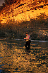 Stock photo of a fisherman flyfishing for rainbow trout on the Guadalupe River in the Texas Hill Country..