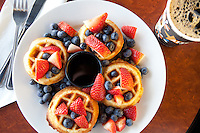 Breakfast waffles with fresh strawberries and blueberries with a freshly poured cup of black coffee at a coffeeshop in St. Louis, MO.