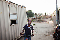 Hal Far, Malta - 20 August, 2012:  A Sub-Saharan migrant ridese his bike between the containers of the Hal Far Hangar Site in Hal Far, Malta, on 20 August, 2012.<br /> <br /> The Hangar Open Center is a field with an ex-aircraft hangar which, until 2011, included Swiss Red Cross tents in a dark, non lit space in very poor conditions and with inflamable oil on the floor. Today, the hangar is closed and the migrants live in 34 external containers with no water. <br /> <br /> The Open Centres in Malta serve as a temporary accomodation facility, but they ended becoming permanent accomodation centres, except for those immigrants who receive subsidiary protection or refugee status and that are sent to countries such as the United States, Germany, Poland, and others. All immigrants who enter in Malta illegally are detained. Upon arrival to Malta, irregular migrants and asylum seekers are sent to one of three dedicated immigration detention facilities. Once apprehended by the authorities, immigrants remain in detention even after they apply for refugee status. detention lasts as long as it takes for asylum claims to be determined. This usually takes months; asylum seekers often wait five to 10 months for their first interview with the Refugee Commissioner. Asylum seekers may be detained for up to 12 months: at this point, if their claim is still pending, they are released and transferred to an Open Center.<br /> <br /> Gianni Cipriano for The New York Times