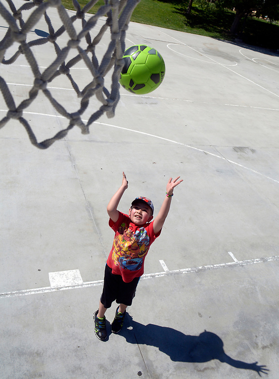 gbs062817d/ASEC -- Joshua Romero, 8, of Rio Rancho shoots baskets with a soccer ball in Tigeux Park on Wednesday, June 28, 2017. His grandmother, Rosie Garcia of Albuquerque, took him to the park. (Greg Sorber/Albuquerque Journal)