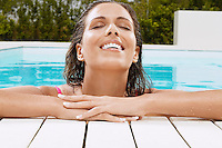 Woman in Swimming Pool resting on poolside close up ground view