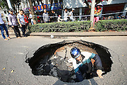 HAIKOU, CHINA - MARCH 17: (CHINA OUT)<br /> <br /> Road Cave-in <br /> <br />  A curious man climbs down a three-meter deep and three-meter diameter hole cave at Qiongzhou Avenue on March 17, 2014, in Haikou, Hainan Province of China. The cave was found around 11 a.m. on Monday. But the cause of the cave is unkonwn till now<br /> ©Exclusivepix
