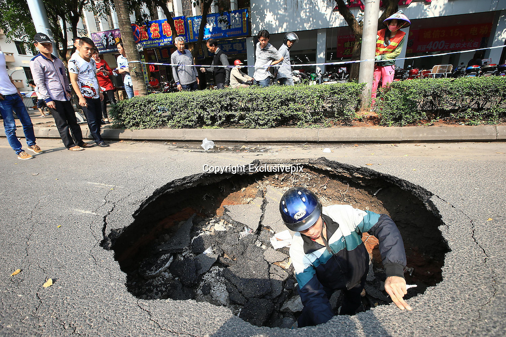 HAIKOU, CHINA - MARCH 17: (CHINA OUT)<br /> <br /> Road Cave-in <br /> <br />  A curious man climbs down a three-meter deep and three-meter diameter hole cave at Qiongzhou Avenue on March 17, 2014, in Haikou, Hainan Province of China. The cave was found around 11 a.m. on Monday. But the cause of the cave is unkonwn till now<br /> &copy;Exclusivepix