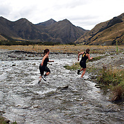 Female runners cross Moke Creek on the Ben Lomond High Country Station during the Pure South Shotover Moonlight Mountain Marathon and trail runs. Moke Lake, Queenstown, New Zealand. 4th February 2012. Photo Tim Clayton