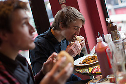 © licensed to London News Pictures. London, UK 15/03/2013. Chris Watkins (left) and Ewan Barker eating 100% horse meat burgers at The Lord Nelson pub in Southwark, London as the pub starts to serve 100% horsemeat burgers to their customers. Photo credit: Tolga Akmen/LNP