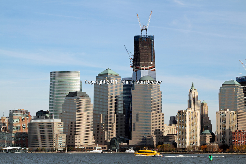 The Freedom Tower under construction and rising from Ground Zero, the scene of the 9/11 terrorist attack. World Financial Center is in the foreground. New York City. As seen from Liberty State Park, Jesey City, NJ, USA