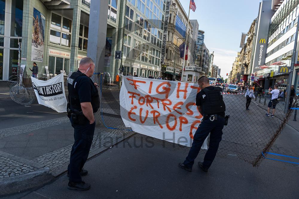 Polizisten entfernen am 10.06.2016 an dem ehemaligen Grenz&uuml;bergang Checkpoint Charlie in Berlin, Deutschland ein Transparent das an einen symbolischen Grenzzaun angebracht ist. Die Aktivisten die die Aktion initiiert haben demonstrieren damit gegen die Abschottungspolitik der EU und die geschlossenen Grenzen. Foto: Markus Heine / heineimaging<br /> <br /> ------------------------------<br /> <br /> Ver&ouml;ffentlichung nur mit Fotografennennung, sowie gegen Honorar und Belegexemplar.<br /> <br /> Bankverbindung:<br /> IBAN: DE65660908000004437497<br /> BIC CODE: GENODE61BBB<br /> Badische Beamten Bank Karlsruhe<br /> <br /> USt-IdNr: DE291853306<br /> <br /> Please note:<br /> All rights reserved! Don't publish without copyright!<br /> <br /> Stand: 06.2016<br /> <br /> ------------------------------Aktivisten bauen am 10.06.2016 an dem ehemaligen Grenz&uuml;bergang Checkpoint Charlie in Berlin, Deutschland einen symbolischen Grenzzaun auf. Die Aktivisten demonstrieren mit der Aktion gegen die Abschottungspolitik der EU  und die geschlossenen Grenzen. Foto: Markus Heine / heineimaging<br /> <br /> ------------------------------<br /> <br /> Ver&ouml;ffentlichung nur mit Fotografennennung, sowie gegen Honorar und Belegexemplar.<br /> <br /> Bankverbindung:<br /> IBAN: DE65660908000004437497<br /> BIC CODE: GENODE61BBB<br /> Badische Beamten Bank Karlsruhe<br /> <br /> USt-IdNr: DE291853306<br /> <br /> Please note:<br /> All rights reserved! Don't publish without copyright!<br /> <br /> Stand: 06.2016<br /> <br /> ------------------------------
