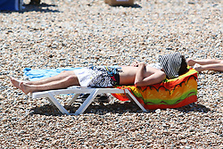 © Licensed to London News Pictures. 10/07/2015. Brighton, UK. People relax and sunbathe on Brighton Beach at the start of a expected warm and sunny weekend, today July 10th 2015. Photo credit : Hugo Michiels/LNP