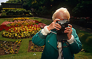 An elderly lady uses a 1970s model of Kodak Instamatic film camera whilst visiting an English country garden. With her eye pressed to the viewfinder, this amateur photographer is a pensioner on a day trip to the country and she takes a snapshot to record the beautiful view of flower beds and neatly-trimmed lawns. The Instamatic was a series of inexpensive, easy-to-load 126 and 110 cameras made by Kodak from 1963 and it was immensely successful, introducing a generation to low-cost photography and helping the growth of the contemporary photographic family album. More than 50 million Instamatic cameras were produced between 1963 and 1970. Kodak even gave away a considerable number in a joint promotion with Scott paper towels in the early 1970s in order to generate a large number of new photographers and stimulate lasting demand for its film business.