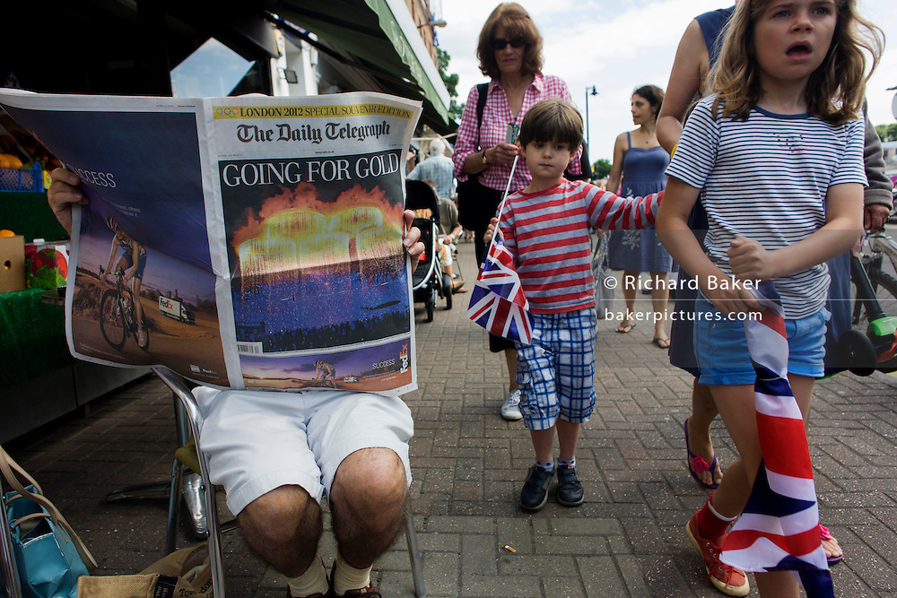 Local children walk past as a reader of the Daily Telegraph newspaper reads about the previous night's Olympic opening ceremony, on the first day of competition of the London 2012 Olympic 250km mens' road race. Starting from central London and passing the capital's famous landmarks before heading out into rural England to the gruelling Box Hill in the county of Surrey. Local southwest Londoners lined the route hoping for British favourite Mark Cavendish to win Team GB first medal but were eventually disappointed when Kazakhstan's Alexandre Vinokourov eventually won gold.