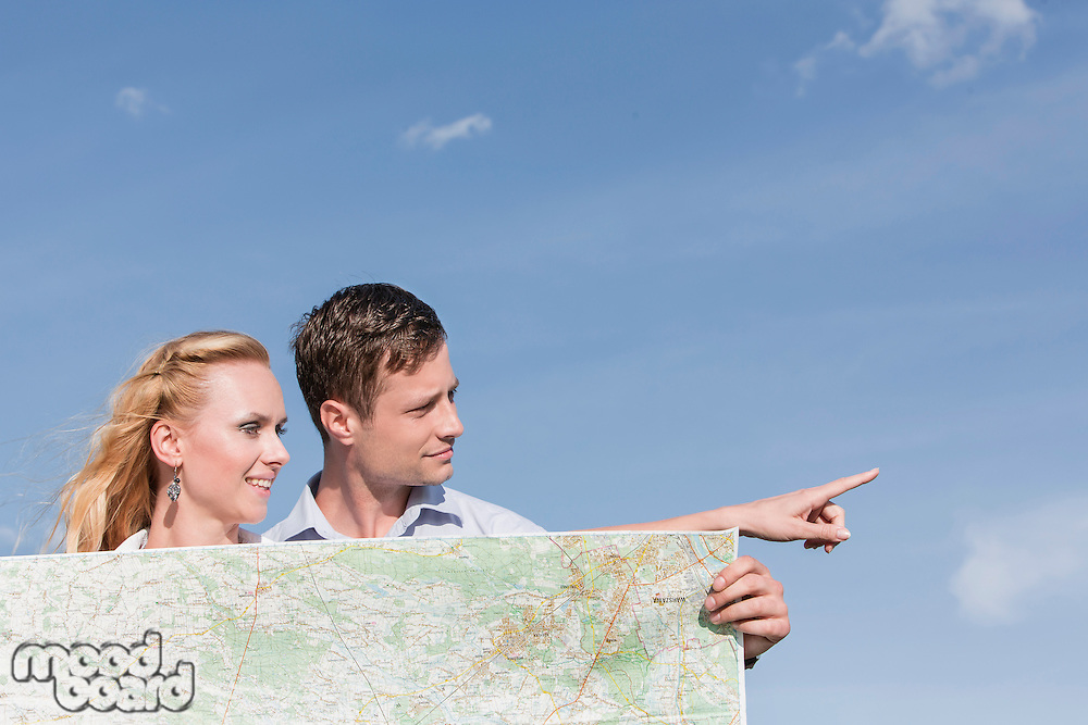 Young man holding map while woman pointing away against sky