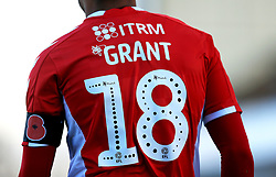 Close up of Charlton Athletic's Karlan Ahearne-Grant shirt with Mind Charity branding and poppy appeal arm band