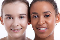 Portrait of two young female friends smiling together against white background