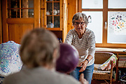 Two pensioners are doing rehabilitation games with a ball in a living room in Oberursel.