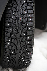Detail of studs fitted to car tyre during winter in Sweden - law requires all road vehicles to fit studded  tyres during winter