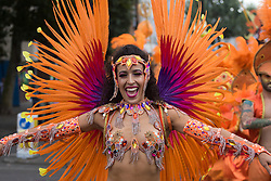 London, August 29th 2016. Bright orange, red and purple feathers make up this woman's costume during day two of Europe's biggest street party, the Notting Hill Carnival.