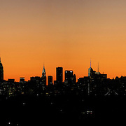 The sun sets behind the Manhattan skyline in New York City viewed from Arthur Ashe Stadium  during the US Open Tennis Tournament, Flushing, New York. USA. 10th September 2012. Photo Tim Clayton