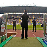 Policing an Old Firm match. Rangers V Celtic, SPL..Celtic park, Sat 19 November 2005..The fourth official (middle) looks on as Gordon Strachan (left( and Alex McLeish (right) watch the match.