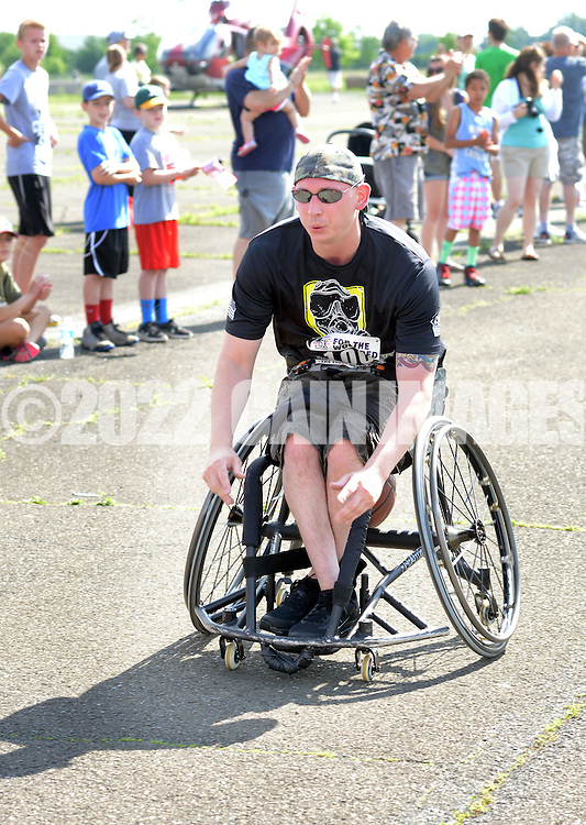 WARMINSTER, PA - JUNE 14: Chris Kile, 32, of Quakertown, Pennsylvania wheels across the finish line during the Wounded Hero 5K to support the Honor & Courage Program of Operation Ward 57 June 14, 2014 at Warminster Community Park in Warminster, Pennsylvania. The event is created to show support for our nation's wounded heroes. (Photo by William Thomas Cain/Cain Images)