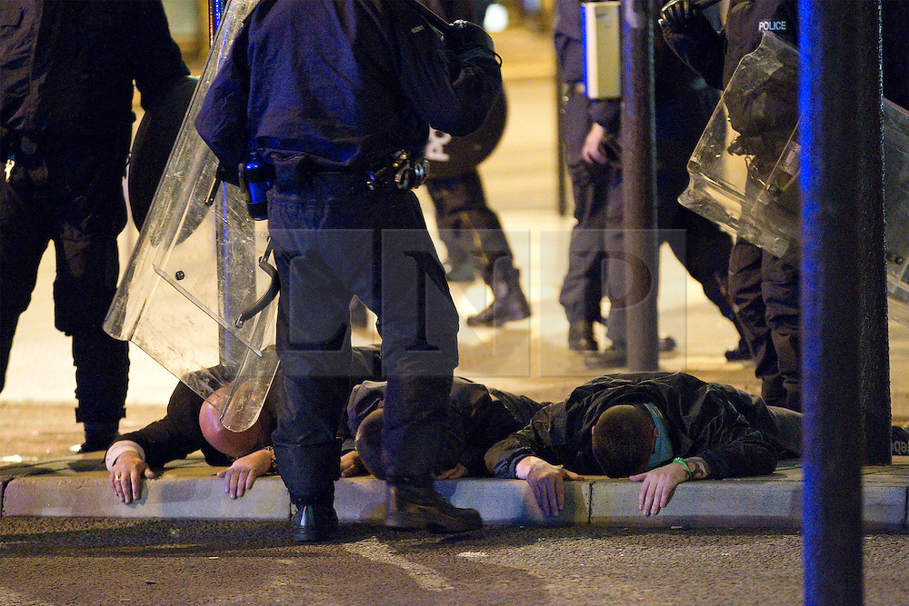 """© Licensed to London News Pictures . FILE PICTURE DATED 09/08/2011 .  Manchester , UK . DOMENYK NOONAN (pictured lying face down, first on the left, being detained by police during riots in Manchester City Centre on 9th August 2011) has been remanded in custody . He is accused of raping a 15 year old boy . He appeared at Manchester Crown Court via videolink from Manchester prison , charged with four counts of rape and false imprisonment . Police were called to a flat in Manchester City Centre on the afternoon of Wednesday (24th October). The organised crime boss and star of documentary """"At Home With the Noonans"""" also goes under the name Lattlay-Fottfoy . He is a cousin of Mark Duggan , whose shooting sparked off riots in London in the summer of 2011 . Photo credit : Joel Goodman/LNP"""