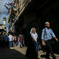 A Palestinian woman walks next to an Israeli man along&nbsp;Hagai&nbsp;Street&nbsp;in Jerusalem's Old City , Thursday, Oct. 8, 2015. The tension on the street has been rising steadily for several years now, particularly in the alleys leading off it to the Temple Mount. That is where Muslim women gather to curse Jews on their way to the Temple Mount and where closely-guarded groups exiting the Western Wall tunnels make their way back to the Western Wall concourse. It is where hundreds of ultra-Orthodox pass on their way to the Western Wall and where hundreds of tourists gather while walking the Via Dolorosa. The street is also one of the two main markets of the Muslim Quarter.<br />
