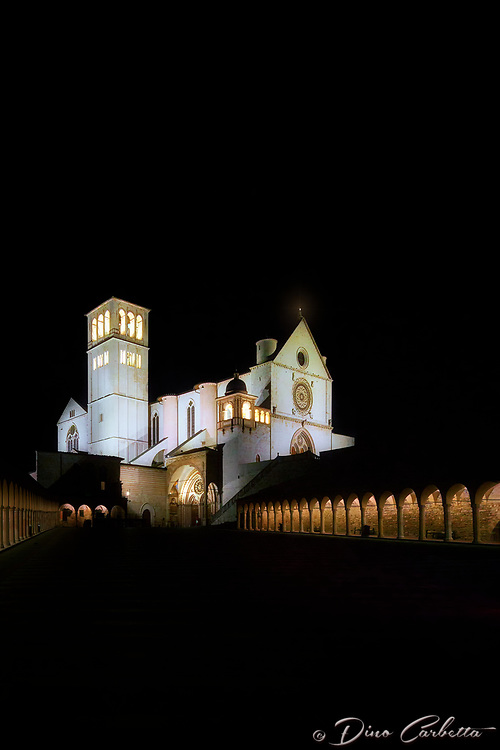"""""""Midnight glow of the Papal Basilica of St. Francis of Assisi""""…<br /> <br /> Upon arrival early that day in Assisi, I began taking photos the second I parked at Hotel Giotto just inside the walls in the foothills of Assisi. Perhaps Saint Francis arranged the dramatically perfect skies and coordinated every encounter. Beginning at the Basilica of Saint Frances, every second of the climb to the top of the mountain to the fortress Rocca Maggiore, a new surprise awaited around every corner.  Never stopping for lunch or dinner, I continued to photograph new images well past sundown.  Traversing the narrow steps and strada back down to the bottom of the mountaintop to my hotel, the walk seemed a bit less strenuous and I felt a sense of gratitude and completion of my day long journey.  However, the very quiet Assisi seemed to have fallen into a deep slumber in the early nighttime leaving all the restaurants closed for the night.  Pleading with the hotel manager, she desperately arranged a late dinner at one of the most iconic restaurants in Assisi, La Locanda Del Cardinale, which was built over an ancient Roman settlement dating from the first century B.C., with glass floors to view the mosaics below.  Walking back at midnight to the hotel, the peaceful Assisi continued to call out.  As the serene, quiet Basilica of Saint Francis stood majestically and glowed in the midnight skies, one could not help but to acquiesce to its mystical yearning for just a few more memorable portraits in the cool dew of the early morning air."""