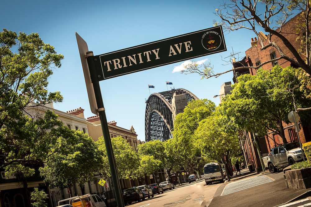 A street sign reading Trinity Avenue dominates the foreground as the metal arches of the Sydney Harbour Bridge rise above the ground in the distance