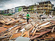 16 SEPTEMBER 2015 - BANGKOK, THAILAND: A laborer sorts through debris from the demolition of traditional shophouses in the Bang Chak Market area, along Sukhumvit Sois 93 and 95 in Bangkok. The Bang Chak Market serves the community around Sois 91-97 on Sukhumvit Road in the Bangkok suburbs. About half of the market has been torn down, vendors in the remaining part of the market said they expect to be evicted by the end of the year. The old market, and many of the small working class shophouses and apartments near the market are being being torn down. People who live in the area said condominiums are being built on the land.     PHOTO BY JACK KURTZ