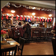 NEWTOWN, CT-10 December 2013- The Iron Bridge<br /> Restaurant and Bar at 100 Church Hill Road offers a $9.95 burger and beer special. A waitress greeting diners doesn&rsquo;t bother with most of the menu, flipping directly to the burger page: a monstrous burger, onion brick and curly fries, served with a 10-ounce mug of draft<br /> Busch. Chatting with regulars sipping noonday beers, the waitress says she made sure to take today off.  (Photo by Robert Falcetti)