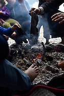 Syrian Kurdish refugees sit around a fire to dry their socks and shoes on a rainy day at Kara Tepe camp near Mytilene, Lesbos, Greece. The camp was established for refugees transiting through Lesbos on their way from Turkey to the heart of Europe.