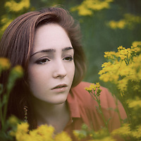 Close up headshot of young woman with sad expression amongst flowers