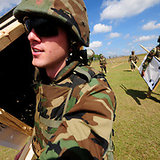 October 16, 2008 -- GULFPORT, Miss. -- U.S. Navy Diver 3rd Class Matthew Wilson carries a target frame off of the pistol range during a transition from the Navy Handgun Qualification Course to the Practical Weapons Course, a firing sequence which utilizes obstacles as part f the course of fire. Wilson is participating in the handgun marksmanship part of the Expeditionary Combat Skills School (ECS).  .The ECS school is designed to build a basic level of battlefield competence for sailors from the Navy's newly formed Expeditionary Combat  Combat Command  (NECC) community. The students have a wide range of precision modern warfare skills. Because the Navy is supporting missions ashore more than ever, there is a significant need for sailors to gain land-based combat skills. The aim of the school is to provide NECC sailors basic warfighting and survival capabilities. Photo by Mass Communication Specialist 1st Class Roger S. Duncan.  (RELEASED)