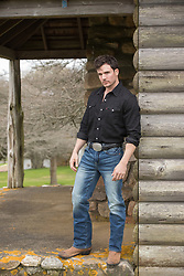 good looking man standing on a rustic cabin porch