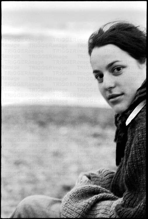 A young woman sitting near the sea wearing a thick jumper