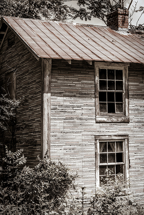 Abandoned house with shingle siding on Highway 150 in Caswell County, North Carolina.