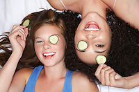 Teenage Girls lying on backs with cucumbers in eyes overhead view