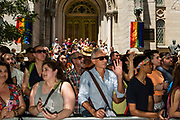New York, NY - 25 June 2017. New York City Heritage of Pride March filled Fifth Avenue for hours with groups from the LGBT community and it's supporters. Spectators in front of the Marble Collegiate Church on Fifth Avenue. Rainbow banners hang from fixtures beside the church entrance.