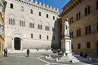 SIENA, ITALY - 20 MARCH 2015: The headquarters of the Monte dei Paschi di Siena bank at Palazzo Salimbeni behind the statue of Sallustio Bandini, an 18th-century Tuscan economist who was an early advocate of free trade, in Siena, Italy, on March 20th 2015. <br /> <br /> Siena, a Tuscan city and UNESCO World Heritage Site, is home to Monte dei Paschi di Siena, the world's oldest surviving bank and Italy's third largest bank. The bank, founded in 1472, was the largest employer in Siena, and it helped finance a host of community projects and services until it stumbled during the financial crisis started in 2008.